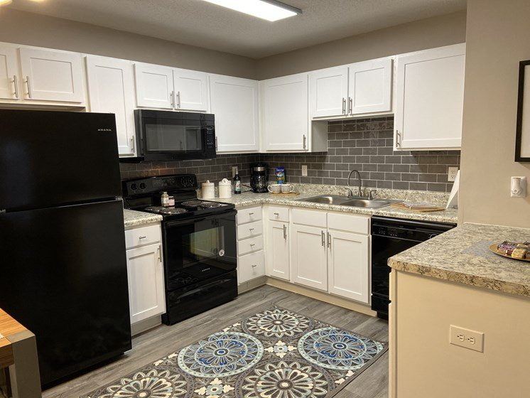 fayetteville NC apartment kitchen with white cabinets and black appliances