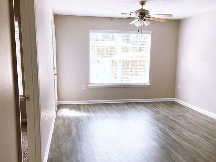 empty apartment living room with wood-look flooring at Crescent Commons in Fayetteville NC