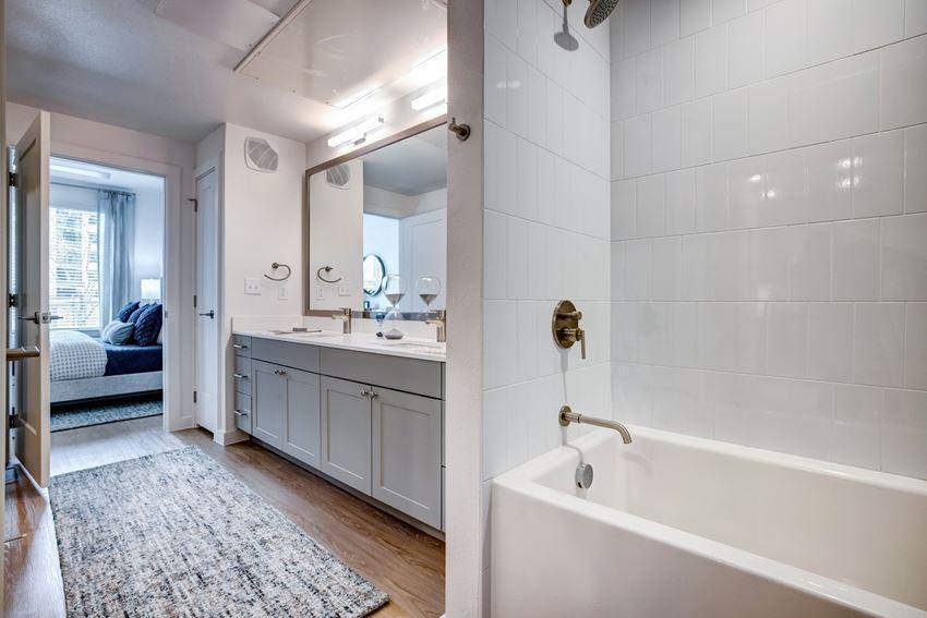 Bathroom with white quartz countertops, grey custom cabinetry, wood style floors, deep soaking bath tub with tile surround, framed bathroom mirror, designer plumbing fixtures