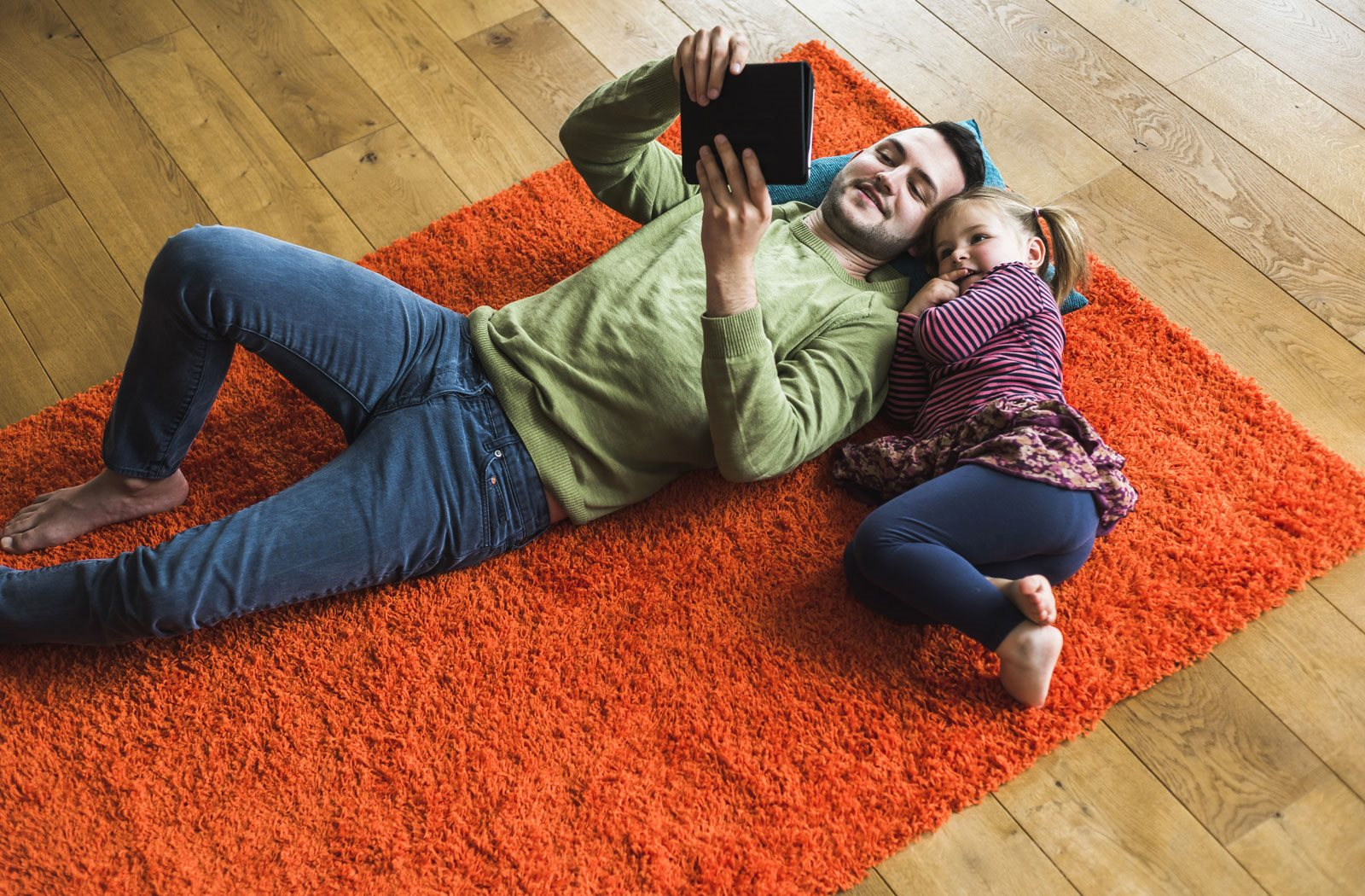Father and daughter, watching a movie on floor, inside Realstar home