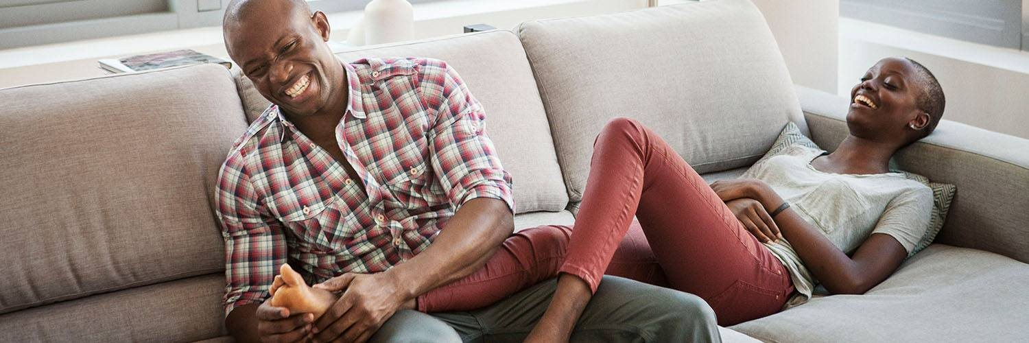 young adult couple laughing on couch