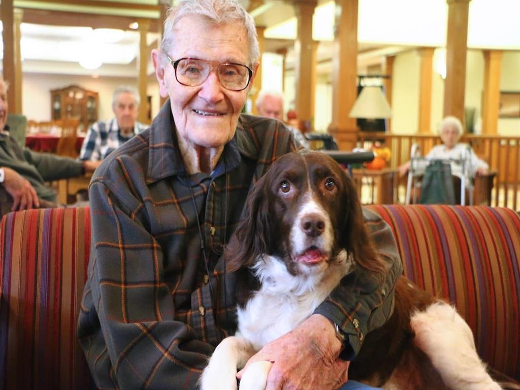 Symphony resident smiling with his pet dog