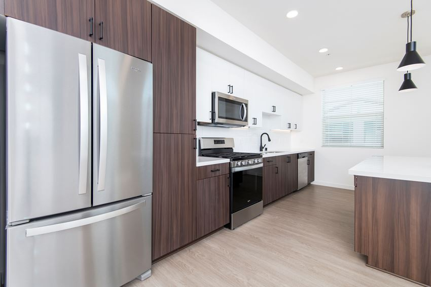 Penthouse kitchen with stainless steel appliances, gas range, white quartz counters, and wood style flooring.