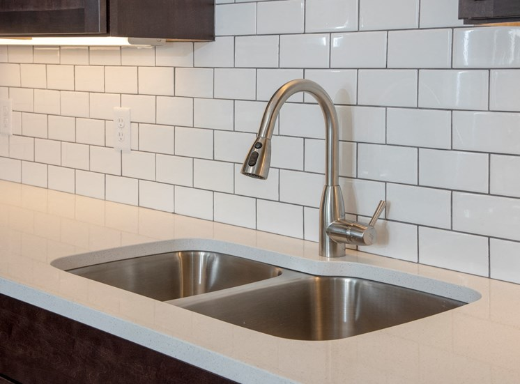 quartz countertops and tile backsplash and undercabinet lighting