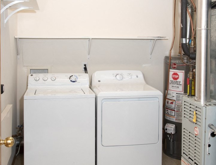 Laundry room with full size washer and dryer and shelving