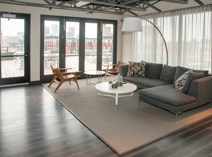 Community Room with Large Grey Sectional And Floor to Ceiling Windows at 700 Central Apartments, Minneapolis, 55414