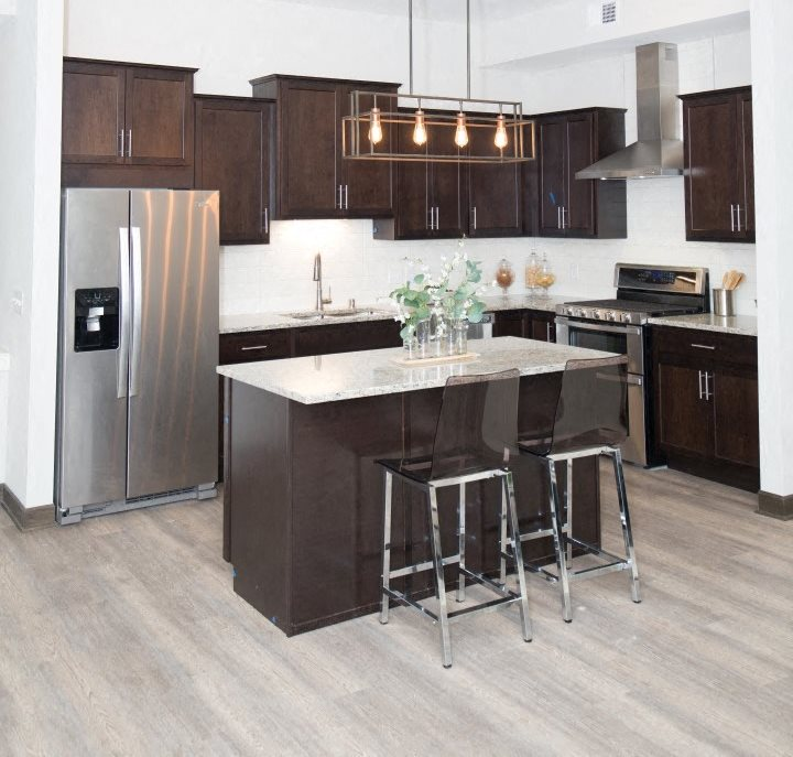 Spacious Kitchen with Island, Stainless Steel Appliances, and Dark Wood Cabinetry