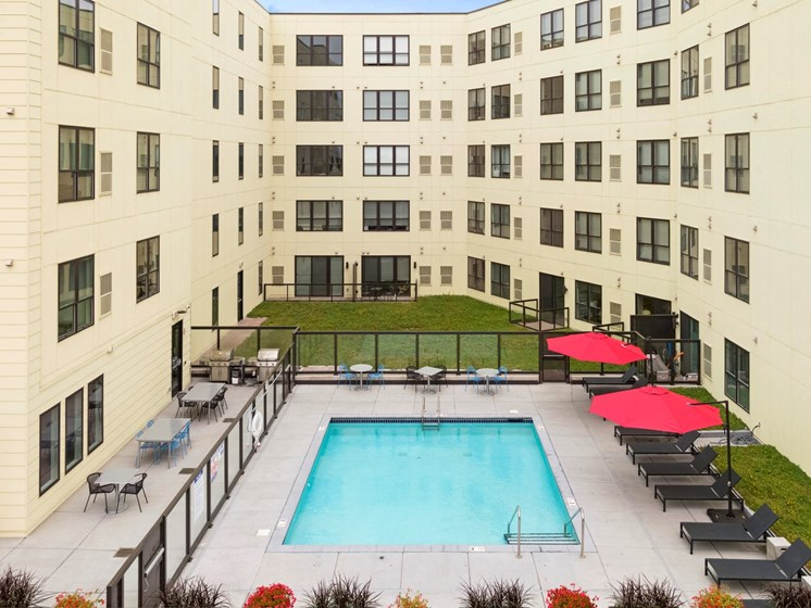 Second Floor Rooftop Pool Deck Surrounded by Grassy Area and Lounge Seating in St. Paul MN