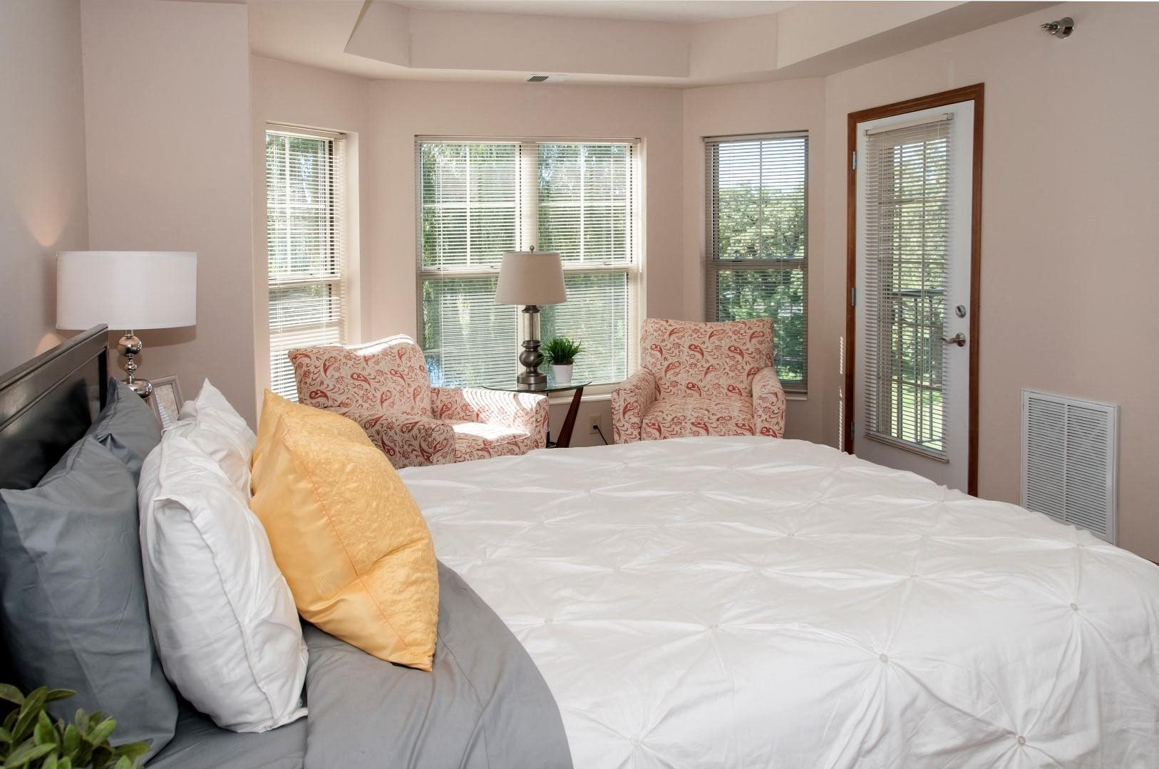 master bedroom with bay windows and patio