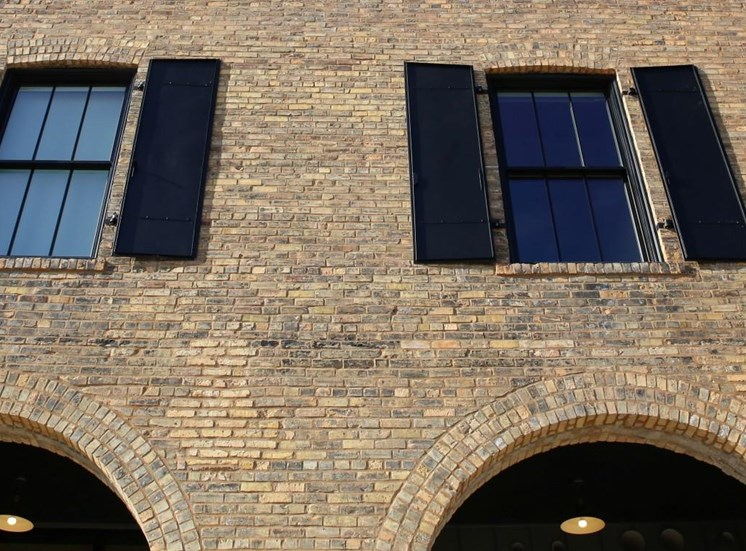 Window Panels with Black Shutters on Brick Exterior at 700 Central Apartments, Minneapolis, Minnesota