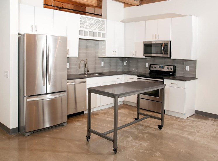 Kitchen with White Cabinetry, Stainless Steal Appliances and Movable Island at 700 Central Apartments, MN, 55414