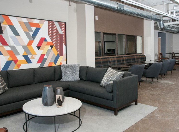 Large Industrial Style Lobby with Various Couches and Colorful Art at 700 Central Apartments in Minneapolis, MN