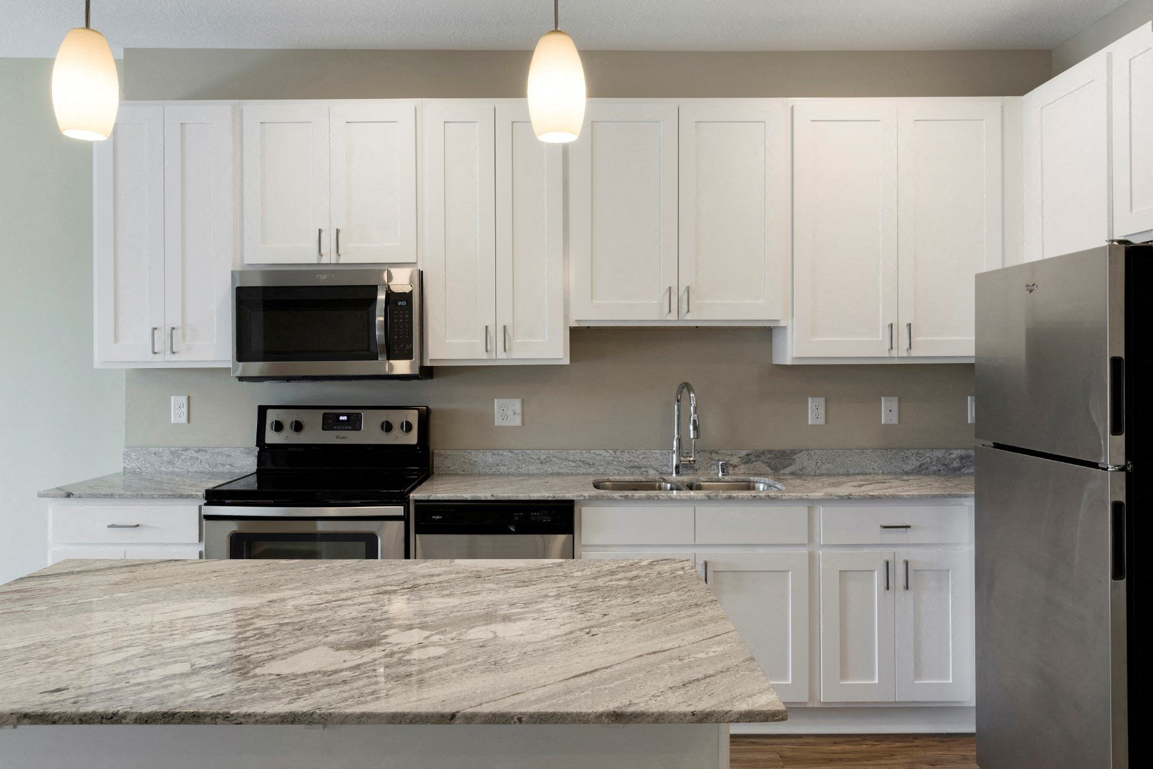 kitchen with white cupboards and island at the liberty apartments in golden valley mn