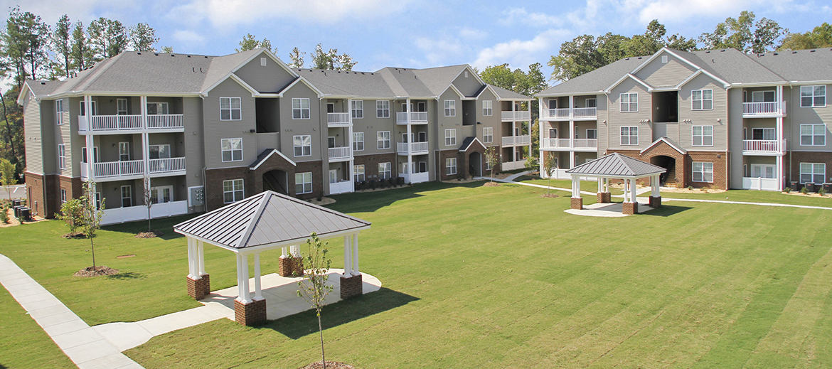 Apartment Buildings Surrounding Grassy Area With Covered Picnic Shelters