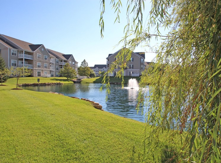 This is a picture of a fountain in a pond with building exteriors at Nantucket Apartments, in Loveland, OH.