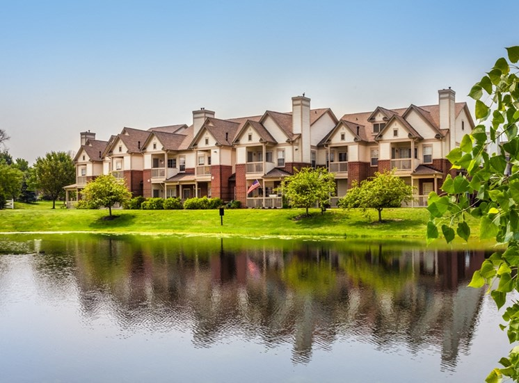 This is a photo of apartment exteriors from across a pond at The Sanctuary at Fishers in Fishers, IN.
