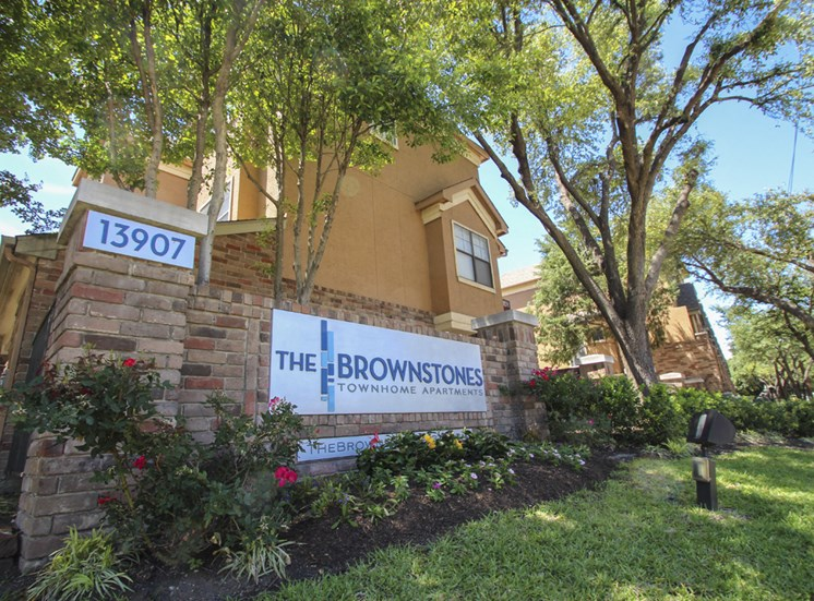This is a photo of the entrance sign at The Brownstones Townhome Apartments in Dallas, TX.
