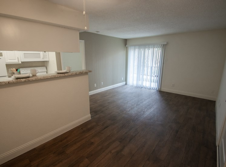 This is a photo of the dining area and living room of the 515 square foot 1 bedroom apartment at Canyon Creek Apartments in Dallas, TX