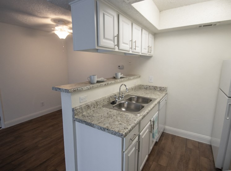 This is a photo of the kitchen  and dining area of the 515 square foot 1 bedroom apartment at Canyon Creek Apartments in Dallas, TX
