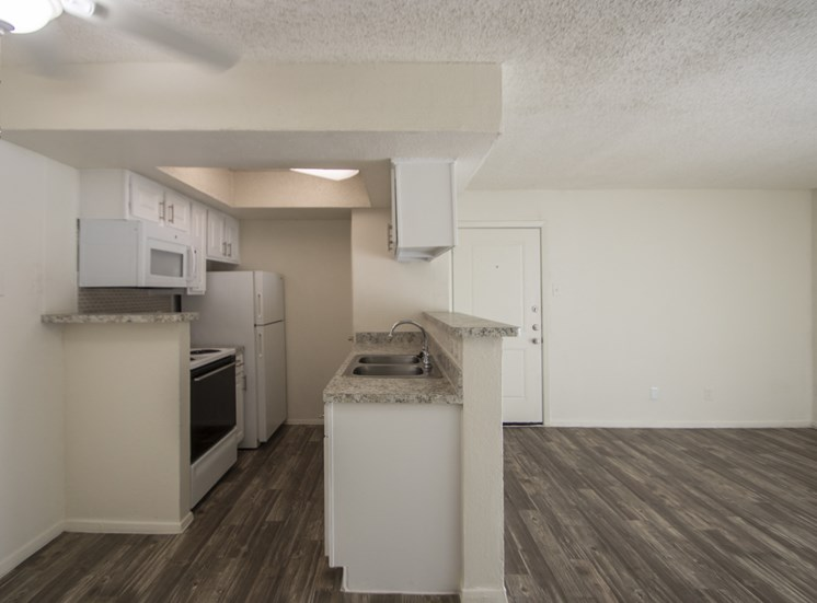 This is a photo of the living room and kitchen of the 550 square foot 1 bedroom apartment at Canyon Creek Apartments in Dallas, TX