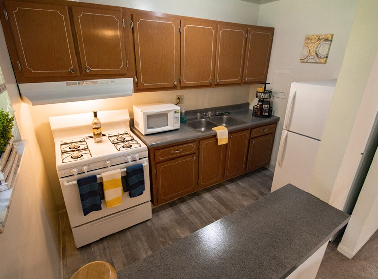 This is a photo of the kitchen of the 550 square foot 1 bedroom, balcony floor plan model apartment at College Woods Apartments in Cincinnati, OH.