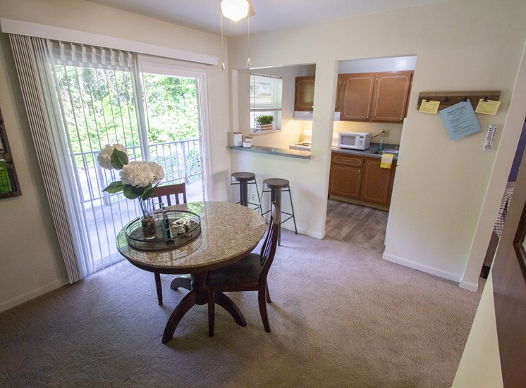 This is a photo of the dining room of the 550 square foot 1 bedroom, balcony floor plan model apartment at College Woods Apartments in Cincinnati, OH.