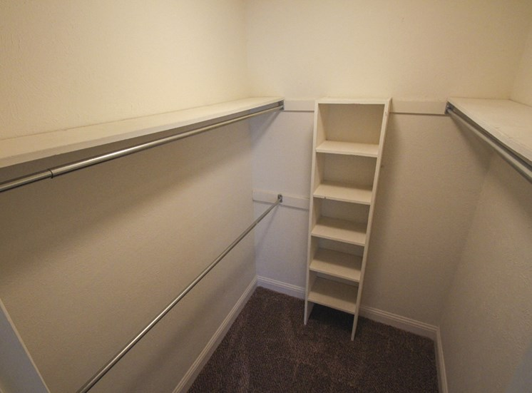 This is a photo of the master bedroom walk-in closet of the 880 square foot 2 bedroom apartment at Canyon Creek Apartments in Dallas, TX