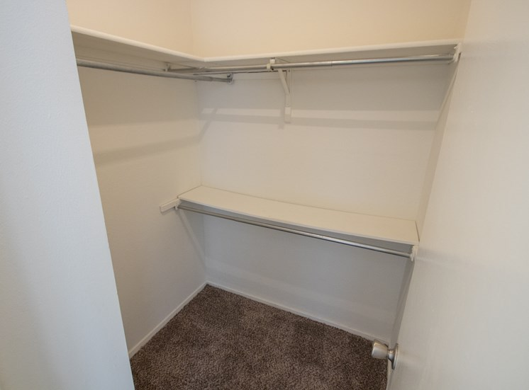 This is a photo of the master bedroom walk-in closet in the 915 square foot 2 bedroom apartment at Gateway Place Apartments in Garland, TX.