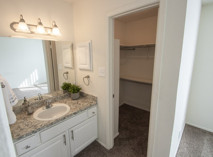 This is a photo of the master bathroom vanity and the walk-in closet in the 915 square foot 2 bedroom apartment at Gateway Place Apartments in Garland, TX.