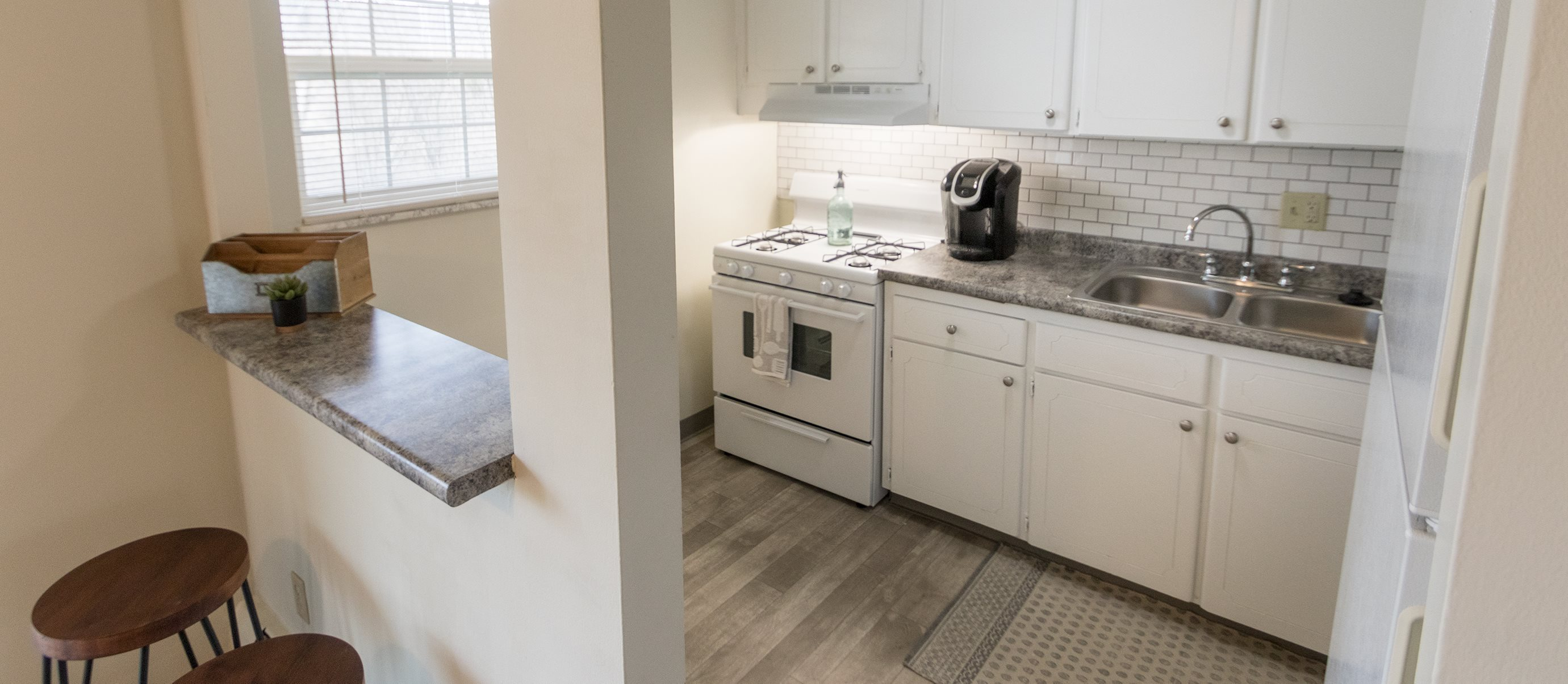 This is a photo of the kitchen and breakfast bar of the 1 bedroom, 631 square foot model apartment at Lake of the Woods Apartments in Cincinnati, OH.