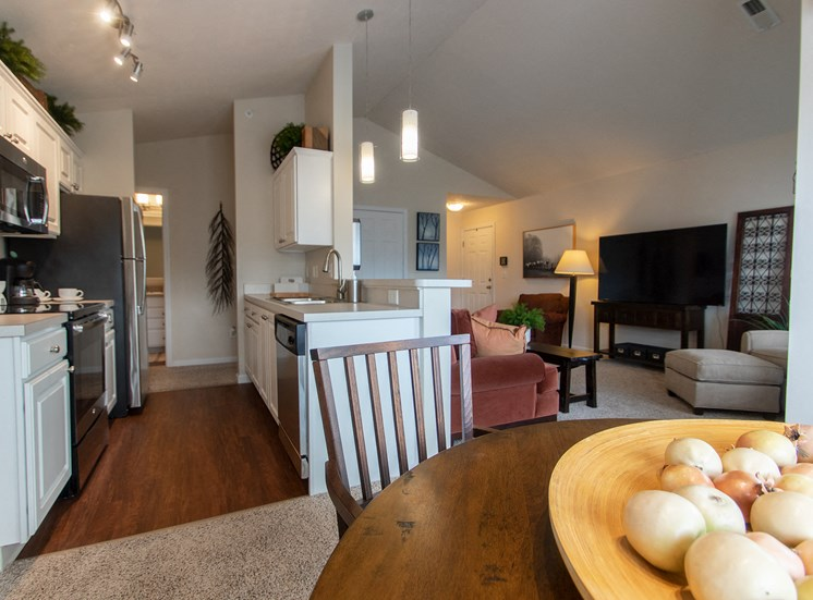 This is a photo of the kitchen and living room from the dining room in the 1016 square foot, 2 bedroom Nautica floor plan at Nantucket Apartments in Loveland, OH.