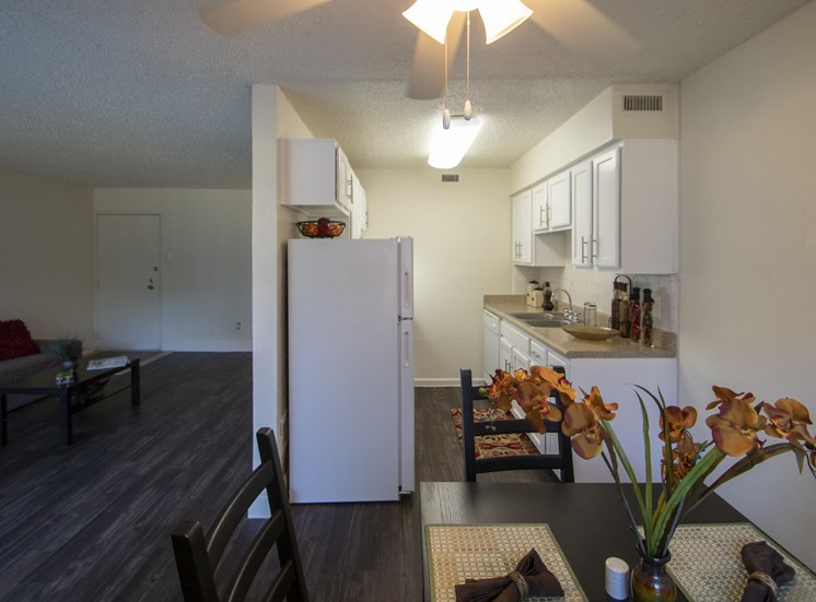 This is a photo of the kitchen and living room/dining area in the 653 square foot 1 bedroom apartment at Princeton Court Apartments in Dallas, TX.