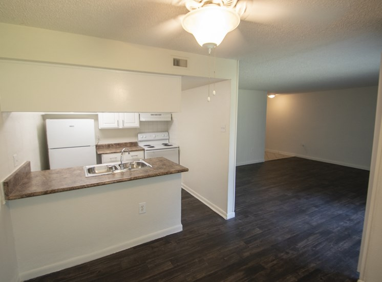 This is a photo of the dining area and living room in the 1060 square foot 2 bedroom apartment at Princeton Court Apartments in Dallas, TX.