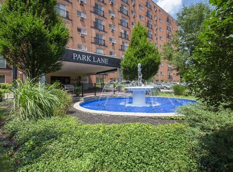 This is a photo of the building exterior featuring the fountain in front of the entrance to Park Lane Apartments in Cincinnati, OH.