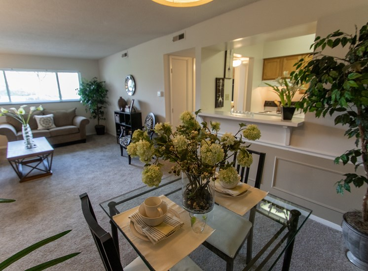 This is a photo of the dining area and living room in the  822 square foot, 2 bedroom floor plan at Village East Apartments in Franklin, OH.