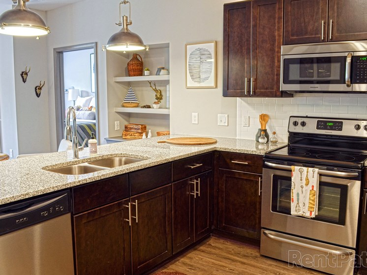 Stainless Steel Appliance Package  with Tile Backsplash in Kitchen