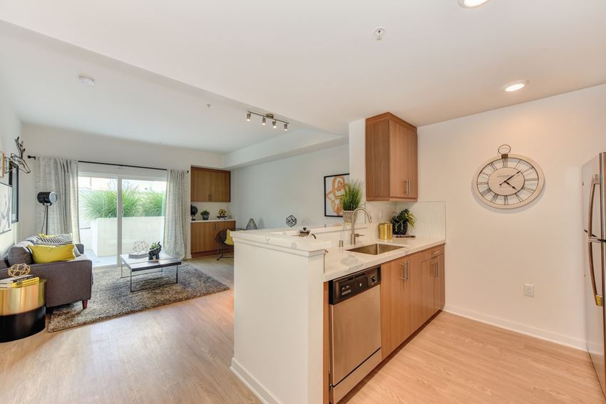 Kitchen overlooking living room area with Hardwood Inspired Floors, Wood Cabinets and Window