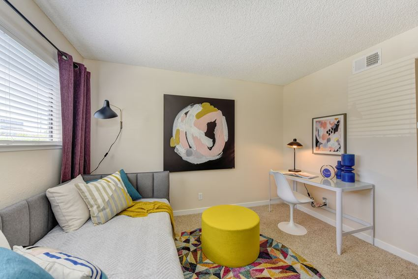Bedroom with Daybed , White Desk, White Chair, Colorful Rug and Yellow Foot Stool
