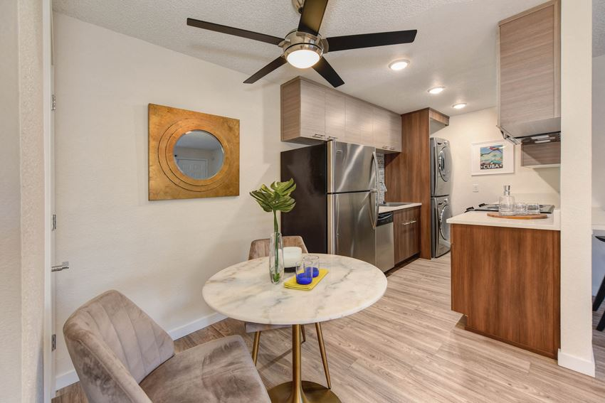 Dining Room with View of Kitchen, Ceiling Fan, White Round Table, Refrigerator and Mirror on Wall