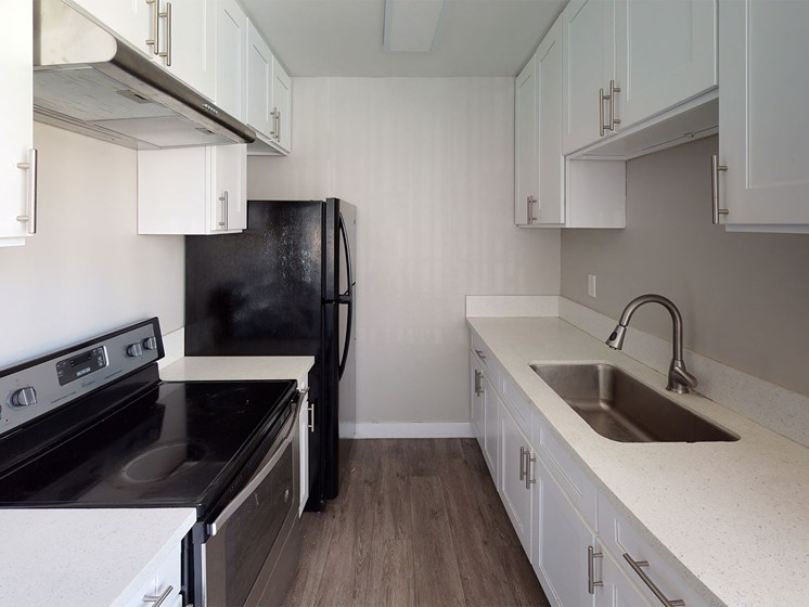 Kitchen With White Cabinetry And Black Appliances at Occidental Apartments, Los Angeles, CA