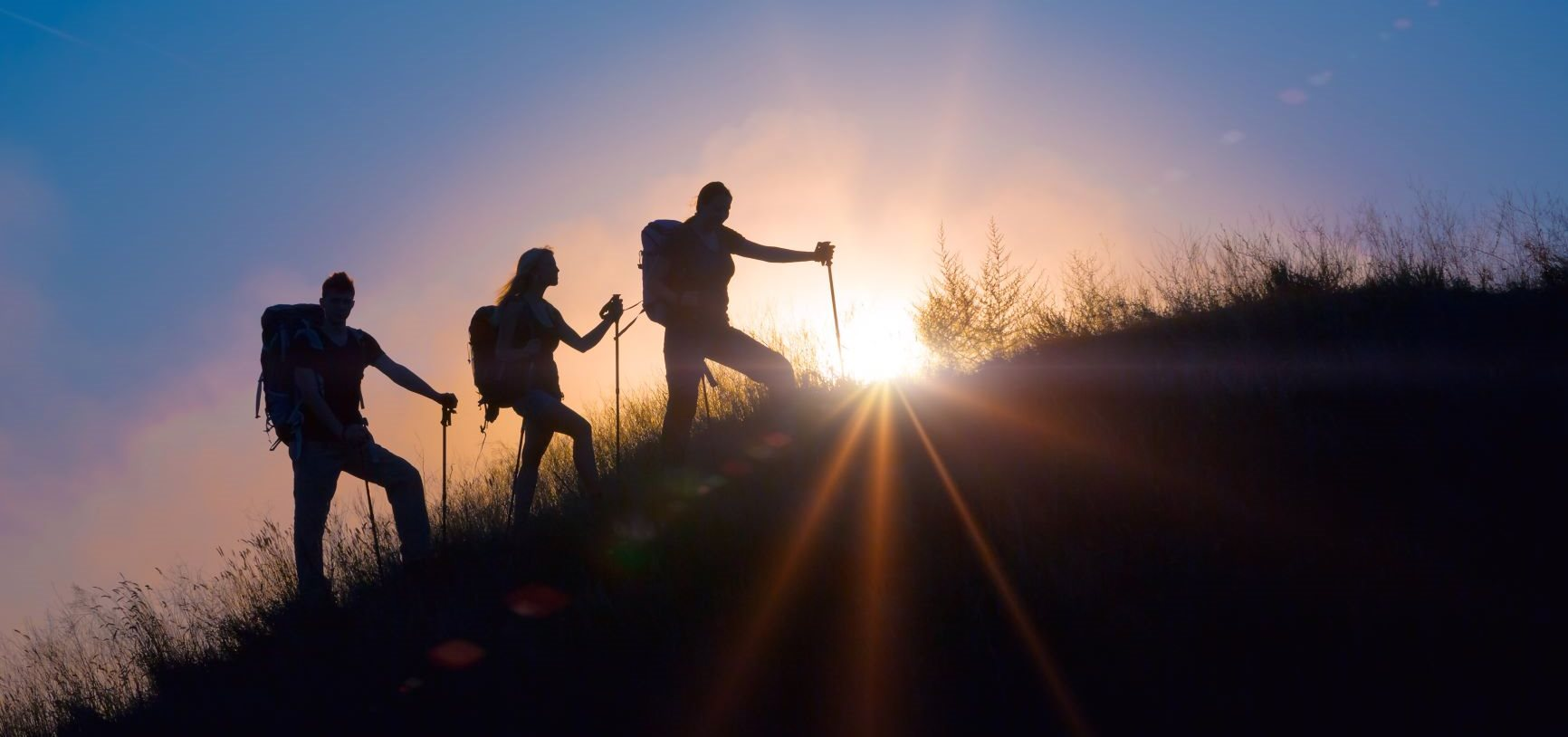 Three people hiking uphill with the sunset behind