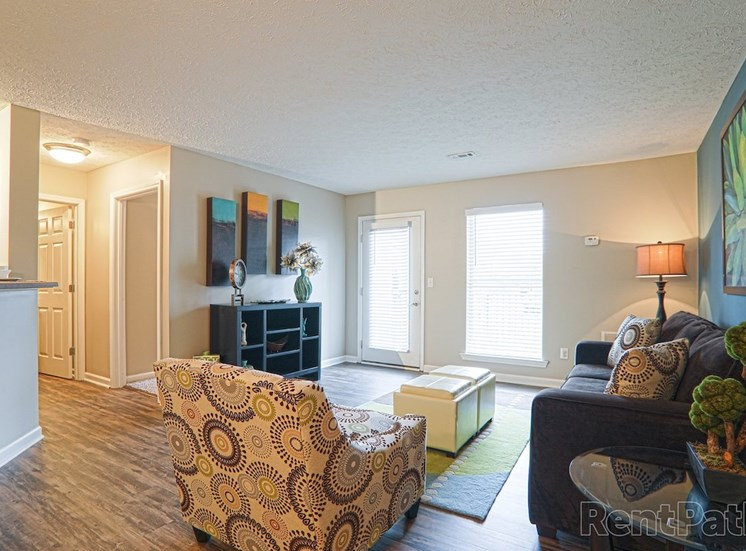 living room with model furnishings, hardwood-style flooring, and door to outside at The Point at Fairview Apartments, Alabama, 36066