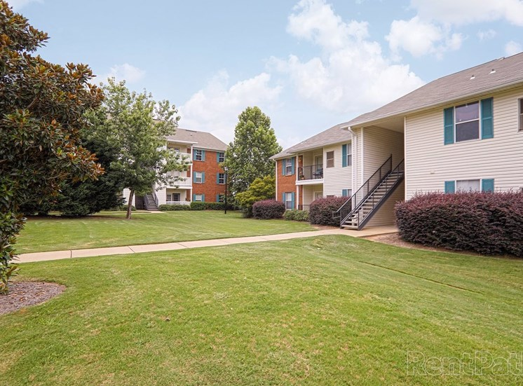 lush landscaping and neat sidewalks outside apartment buildings at The Point at Fairview Apartments, Prattville, AL, 36066