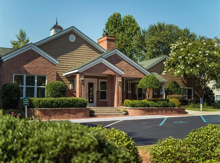 beautiful brick clubhouse surrounded by mature tees and neat landscaping