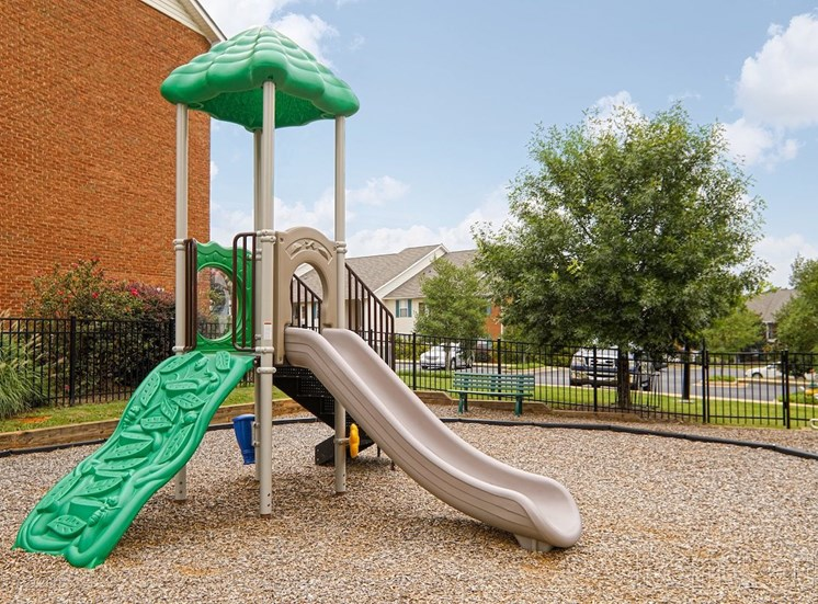 Fenced playground with modern equipment at The Point at Fairview Apartments, Alabama, 36066