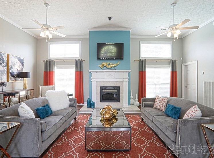 Clubhouse interior with comfortable seating, large windows, and fireplace at The Point at Fairview Apartments, Prattville, Alabama