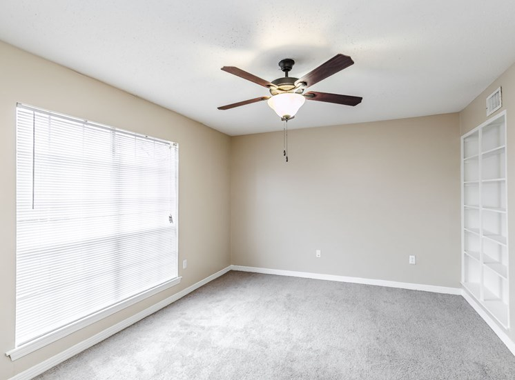 living room with large window, ceiling fan, and built-in shelves at Hampton House Apartments, Jackson, 39211