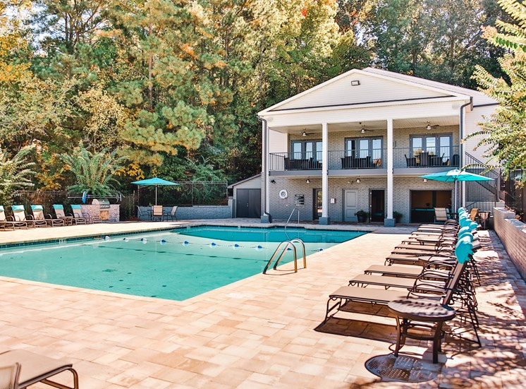 Pool with large sundeck and lounge chairs with clubhouse at The Jameson Apartments, Alabama, 35209