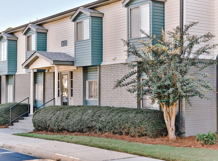 outside of apartment homes with lush landscaping and parking at The Jameson Apartments, Homewood, 35209