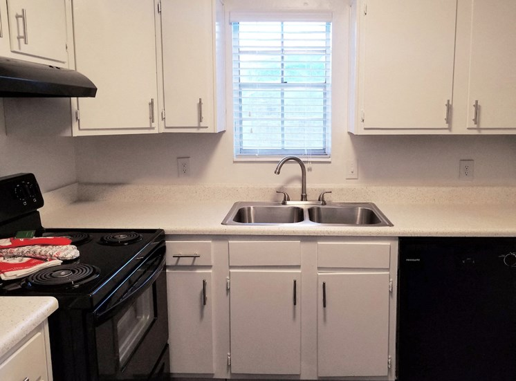 kitchen with black appliances, stainless steel sink, and white cabinetry